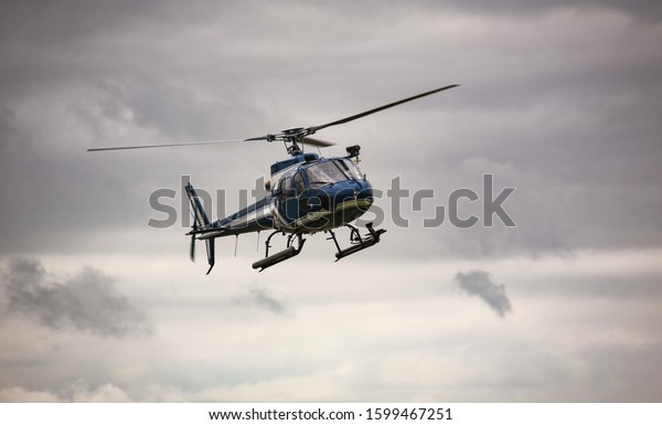 Blue helicopter in flight over a gray sky