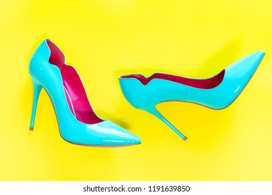 Blue high heels glassy shoes on yellow background, top view