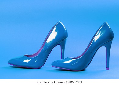 Blue high heels sexy shoes are on blue background.
