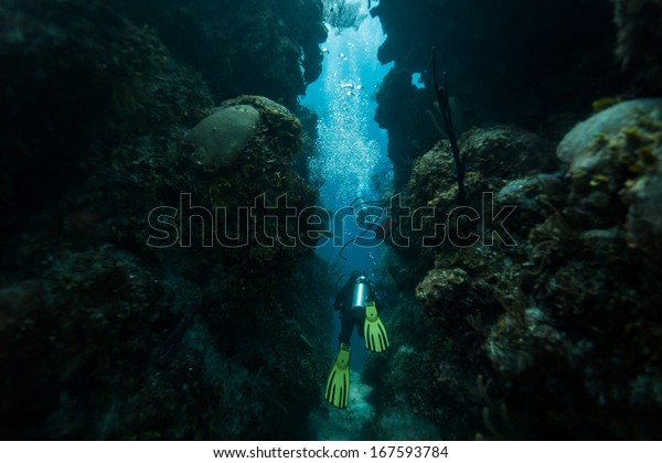 BLUE HOLE, BELIZE - NOVEMBER 26: Scuba diver swims through tunnel on November 26, 2013 in Blue Hole, Caribbean Sea, Belize