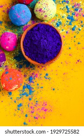 Blue holi powder in bowl and multicolors ball isolated on yellow background