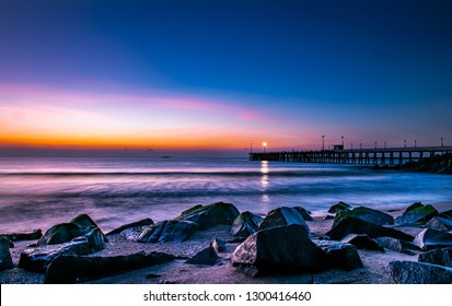 Blue Hour before the sunrise along the pier and the lamp in the pier looks like the star on the rocky shore in puducherry