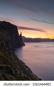 Blue hour beginning to lighten up the cold Atlantic Ocean and coastline with vibrant morning colours, right by Trøllkonufingur also known as Witches Finger, Vagar, Faroe Islands.