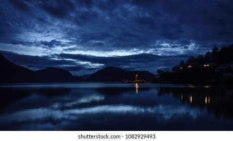 Blue hour in the dock of Caleta Tortel. The Pacific ocean coast can be appreciated. There are some figures of fiords, also lights and smoke coming from a chimney. Patagonia, Chile.