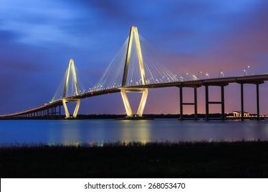 Blue hour image of the illuminated Arthur Ravenel Bridge over the Cooper River in South Carolina, connecting downtown Charleston and Mount Pleasant.