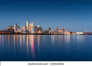 A blue hour image of the Liverpool skyline with lights reflected in the river Mersey