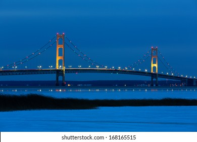 Blue Hour, just after sunset, creates an inviting backdrop for the Mackinac Bridge. Its lights twinkle and create reflections on winter ice. Snow and grass in the foreground add to this fine art photo