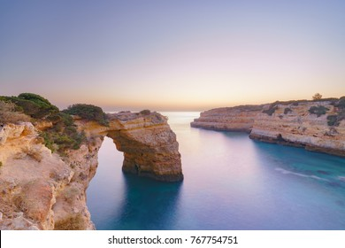 A blue hour long exposure shot shortly after sunset at a rock arch at the Algarve coast in Portugal. Praia da Albandeira.