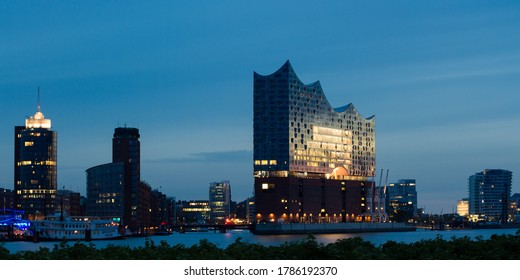 blue hour at the river Elbe in Hamburg, Germany with the office buildings of the Hafencity and the famous music hall Elbphilharmonie in the background