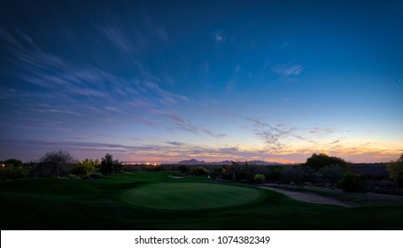 Blue hour in Scottsdale, Arizona.  The image captures a golf course landscape with a dramatic cityscape and sunset in the background.