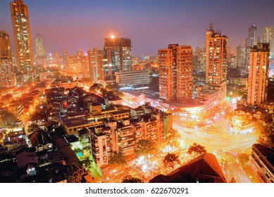 Blue hour shot of a busy traffic intersection in South Mumbai with old, traditional low cost dwellings of lower middle class citizens in foreground and newer towers of elite in background