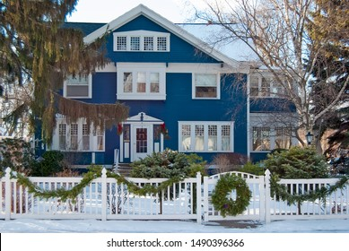 blue house with Christmas wreath on fence gate in winter