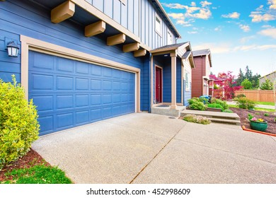 Blue house exterior. View of garage with concrete floor driveway and porch with red entrance door.