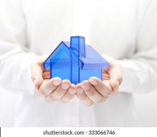 Blue house in hands. Home insurance concept.