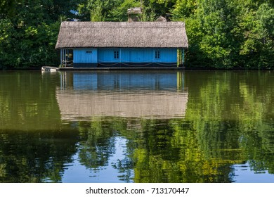 Blue house has a reflection on a river with quiet water