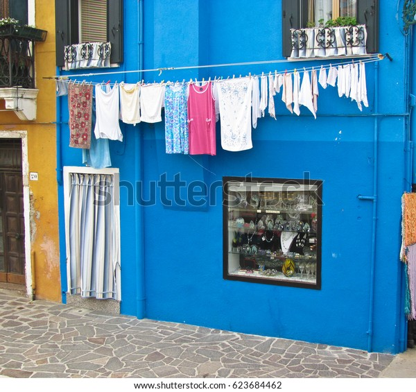 Blue house in Island near Venice in Italy with the laundry drying on a wire