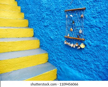 Blue house wall with shell decoration over yellow stairs on the ilsland of Santorini, Greece.