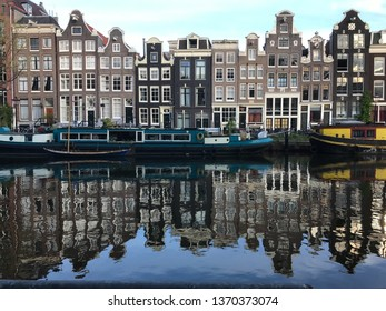Blue houseboat on the Singel canal in Amsterdam