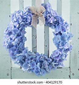 Blue hydrangea flower wreath on vintage wooden background