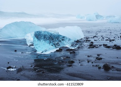 blue ice blocks laying on black sand and pebbles