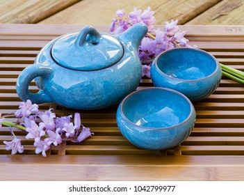 Blue ice crackle glazed ceramic tea pot with two tea cups on a tray decorated with flowers