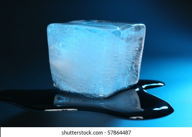 blue ice cube melting in front of dark background