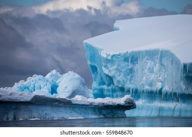 Blue ice with dark clouds behind.