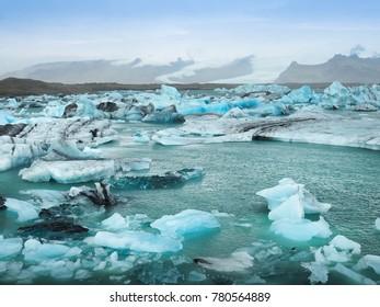 Blue iceberg in Jokusarlon lagoon with background of glacier mountain, Iceland