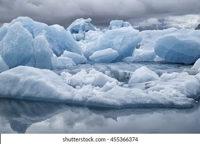 Blue icebergs floating the glacial lagoon in southeast Iceland in summer, blue water in the foreground with copy space and mountains and glacier in the background.