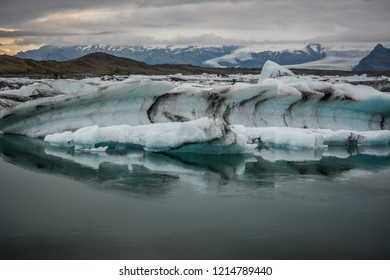 Blue icebergs floating in Jokulsarlon glacial, Iceland in summer at dusk, reflections in the water.