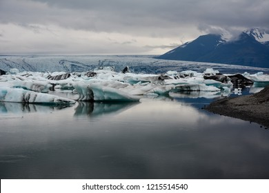 Blue icebergs floating in Jokulsarlon glacial, Iceland in summer at dusk, reflections in the water. With a bit of grain.