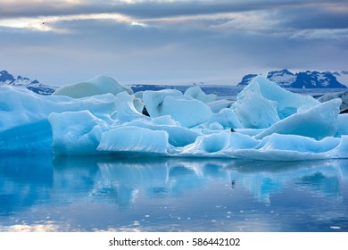 Blue icebergs reflecting in still water on a sunset at glacier lagoon, Jokulsarlon, South Iceland
