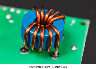 Blue inductor. Magnetic ferrite core detail. Open electric device. Induction coil with copper wire winding. Toroidal electronic part in green circuit board on black background. Electrical engineering.