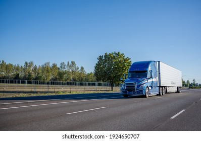 Blue industrial long haul big rig semi truck with high cabin transporting frozen cargo in refrigerator semi trailer driving on the wide multiline interstate highway road with trees on the side