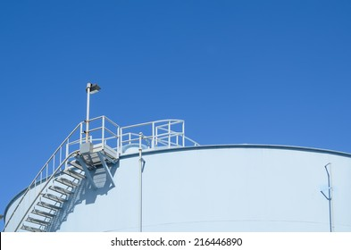 Blue industrial storage tank against cloudless blue sky