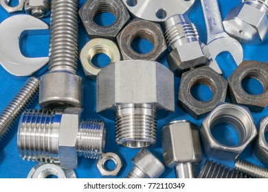 Blue industry or construction abstract background with various bolts and nuts on table.