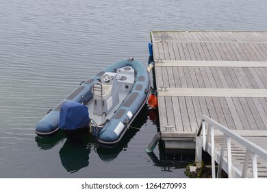 blue inflatable boat moored at the pier