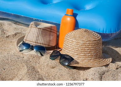Blue inflatable floater, sunscreen cream, sunhats and sunglasses at the sand.