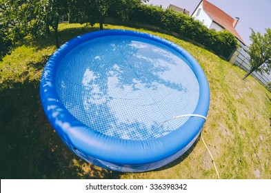 Blue inflatable pool in the village garden in summer time