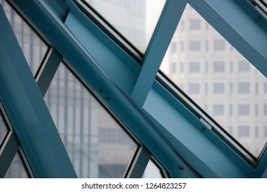 Blue iron beams crisscrossing each other in the Seattle public library with city buildings framed in the background. Capturing the architecture of iconic downtown Seattle.