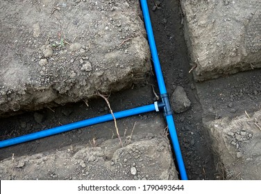 Blue irrigation pipe in trenches connected with a tee fitting