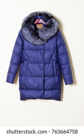 A blue jacket with a hood with a hood on natural fur, isolated on a white wall background. Stylish women's outerwear.