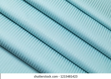Blue jacquard sateen fabric with development in a thin strip is decoratively laid in folds