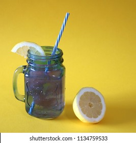 Blue jar of watermelon lemonade with a freshly cut lemon next to it on a yellow colored background