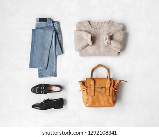 Blue jeans, beige knitted sweater, bag, black loafers or flat shoes on grey background. Overhead view of women's casual day outfit. Flat lay, top view. Women clothes.