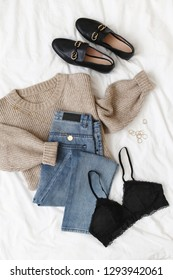Blue jeans, beige knitted sweater, black lace bra, black loafers or flat shoes lying on bed on white sheet. Overhead view of women's casual day outfit. Trendy women clothes. Flat lay, top view.