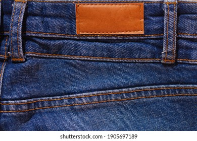 Blue jeans with a blank label and brown stitching. Jeans pocket.