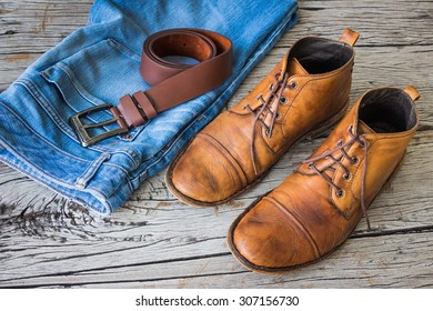 Blue jeans and boots on wooden background