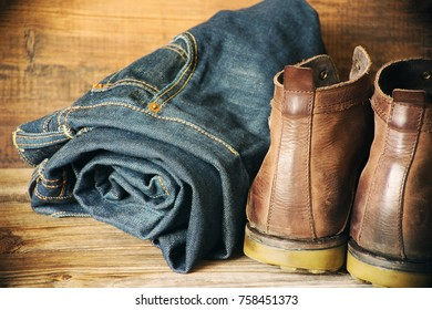 Blue jeans and brown leather men's boots on a wooden surface, close up