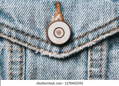 Blue jeans denim fabric. Grunge fashion background pattern with closeup on metal button.